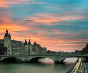 Photo of a car bridge in France with orange and blue sunset in background.